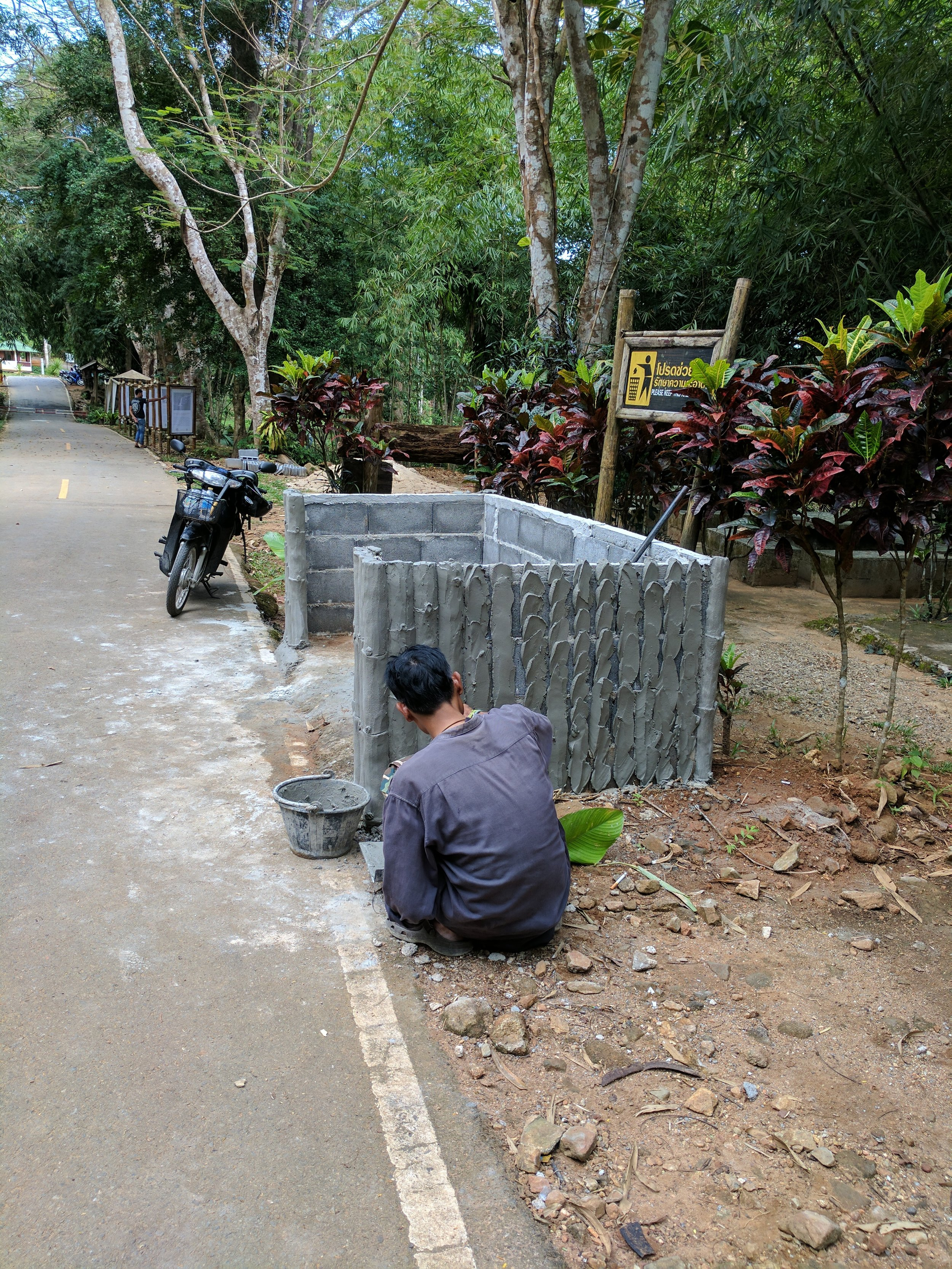 In a national park in Phuket, I passed a worker creating a cement fence around some trash cans.