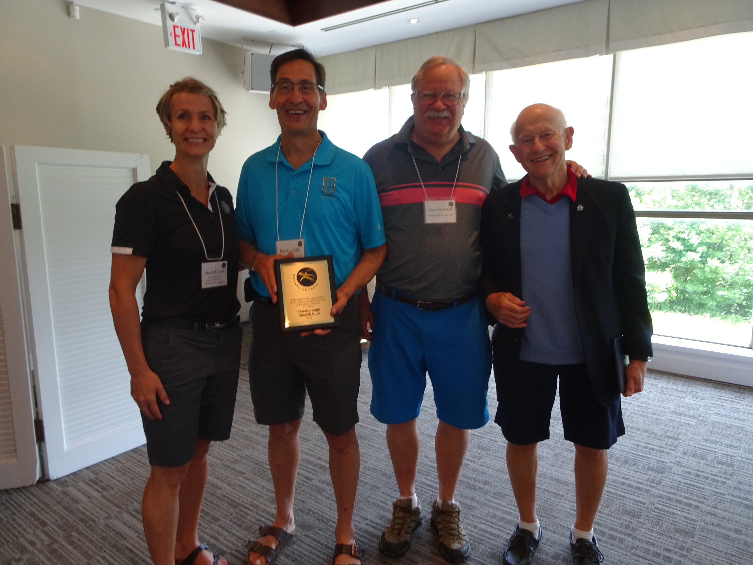 Ray Kerslake accepting the Peterborough Squash Club award pictured with Squash Ontario Board Member Nicole Garon, Canadian Officiating Committee Chair and PSC member Dave Howard, and nominator Vincent Taylor.