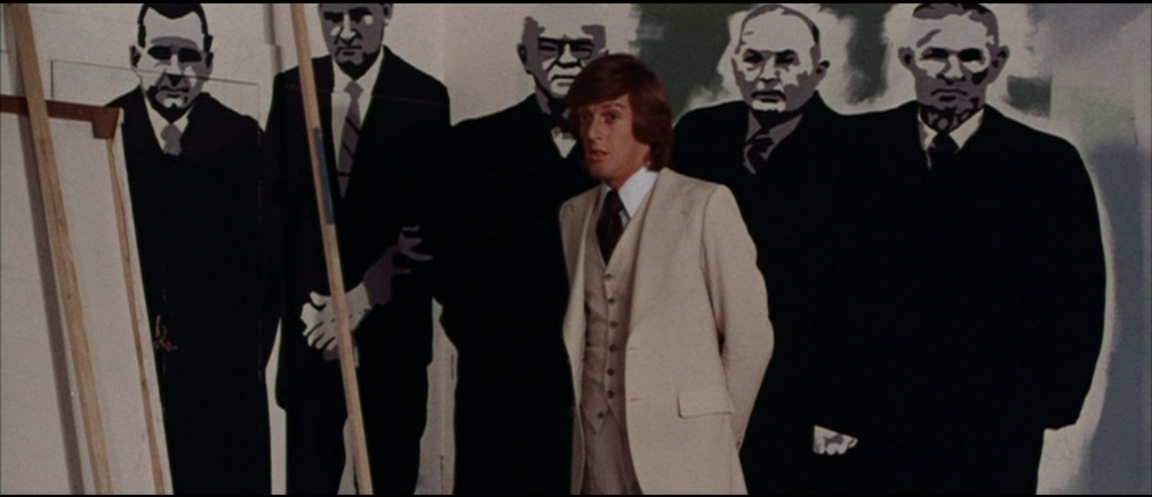 Thom (Michael Greer) stands before one of Arletty's father's paintings — suit-clad men who eerily resemble the film's flesh-eating ghouls.