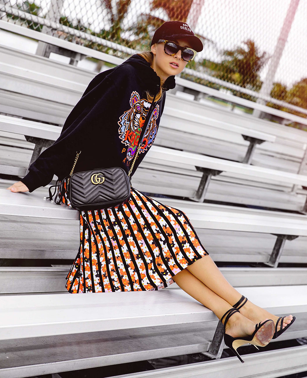 orange-midi-skirt-vertical-stripe-black-sweater-sweatshirt-hoodie-graphic-black-bag-blonde-sun-hat-cap-black-shoe-sandalh-fall-winter-lunch.jpg