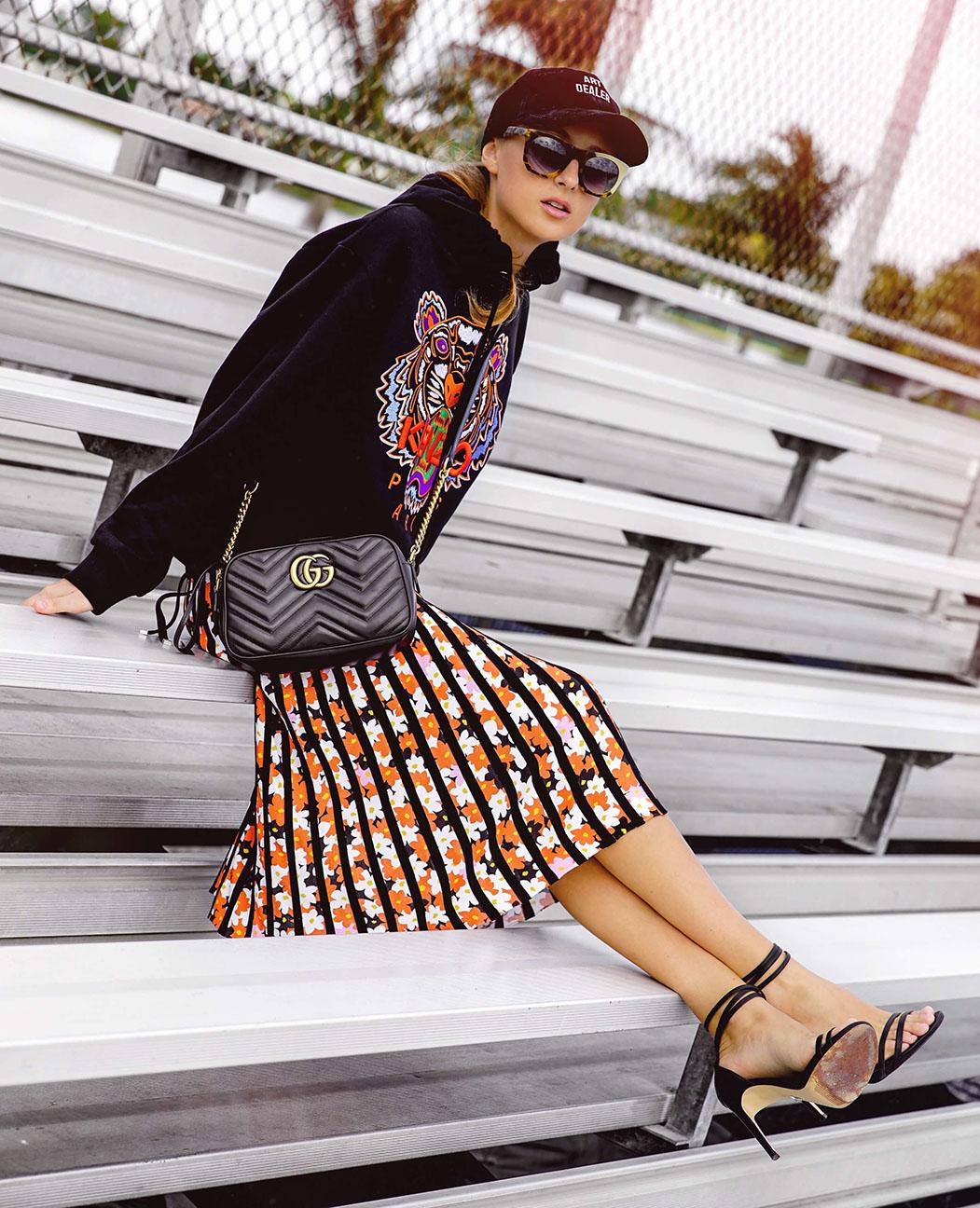 orange-midi-skirt-vertical-stripe-black-sweater-sweatshirt-hoodie-graphic-black-bag-blonde-sun-hat-cap-black-shoe-sandalh-fall-winter-lunch.jpg