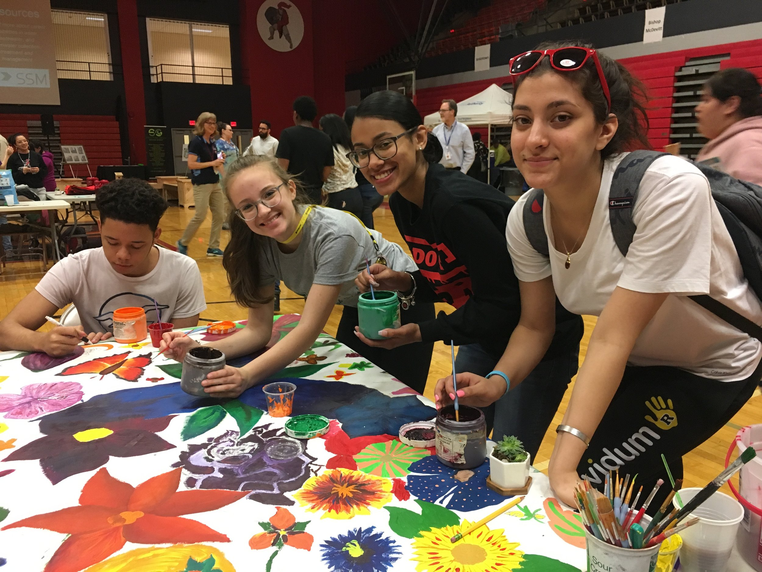 Art students paint a mural for the new courtyard.
