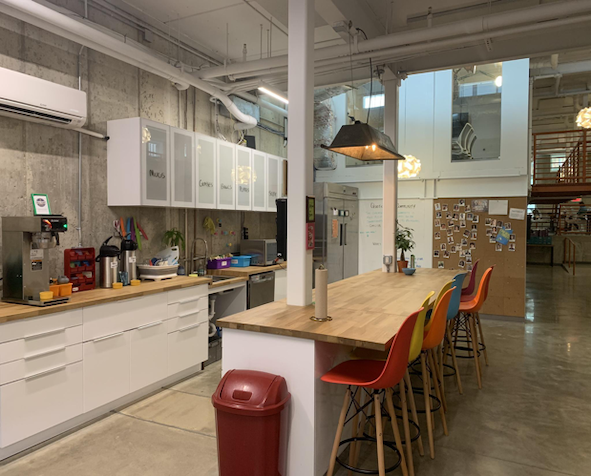 The stocked kitchen holds a variety of organic teas and fresh coffee. Open counter space encourages members to sit and socialize.