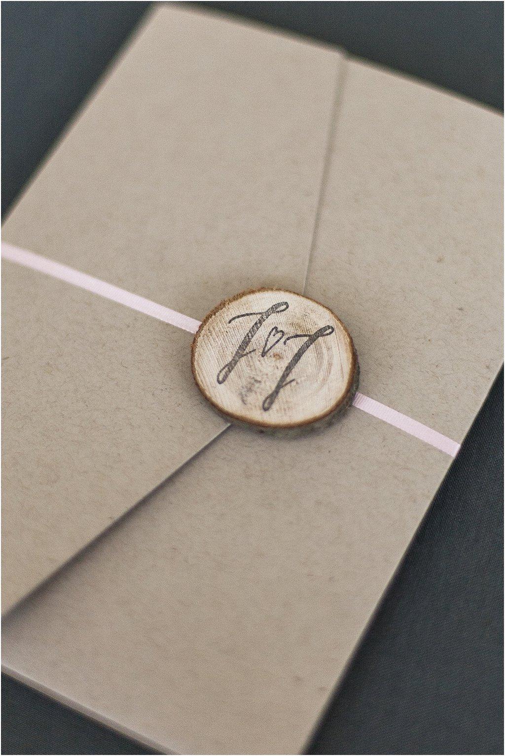 Pocketeinladung geschlossen mit Band und Holzscheibe und gestempeltem Paarlogo