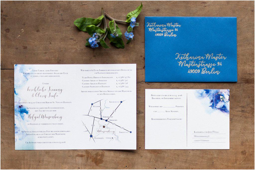 Einladung offen und Rückseite Antwortkarte mit blauem Umschlag, der Gold beschriftet ist.