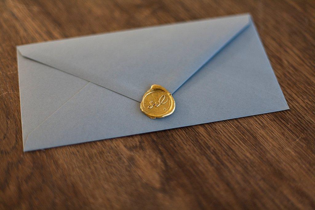 Grauer Briefumschlag mit Siegelstempel Gold