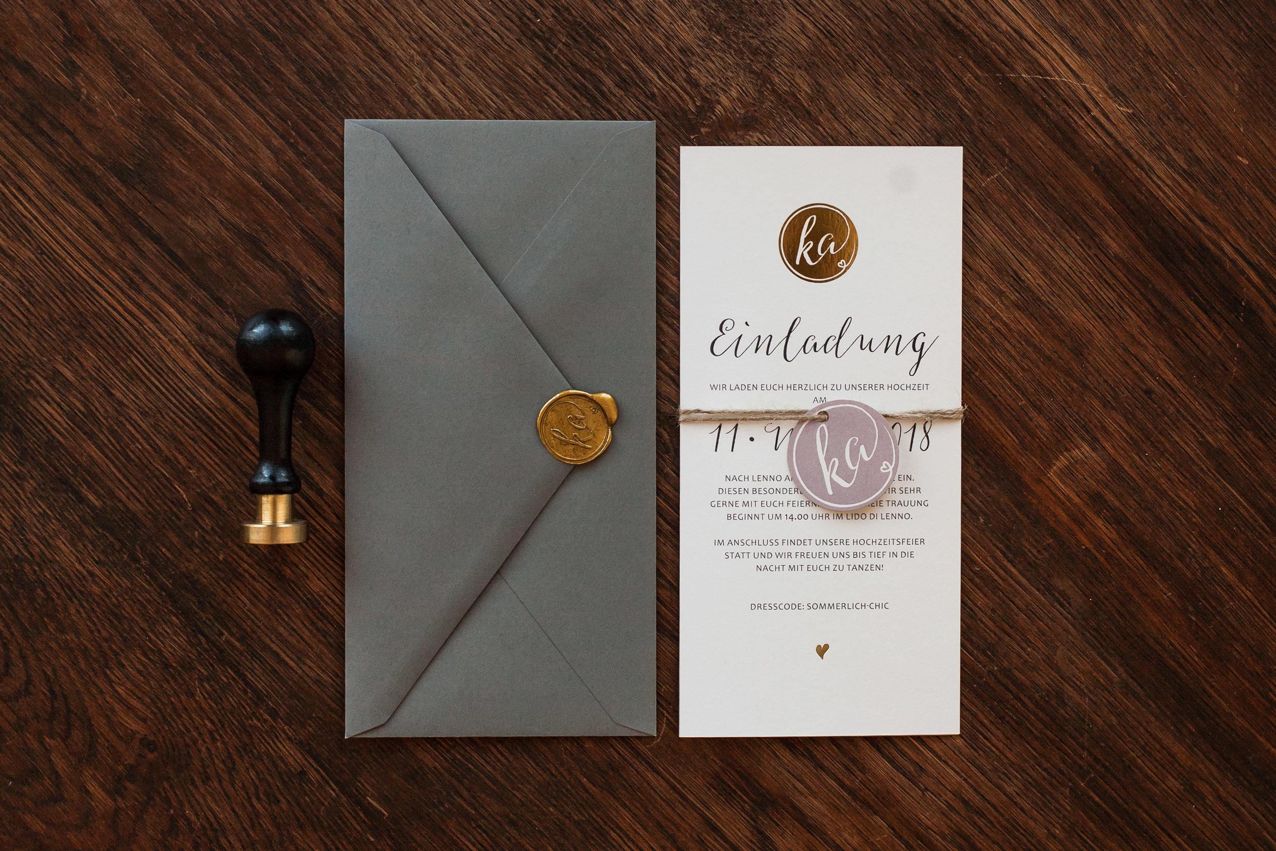 Hochzeitseinladung aus zwei Flachkarten gebunden mit Anhänger, grauer Briefumschlag mit goldenem Siegel