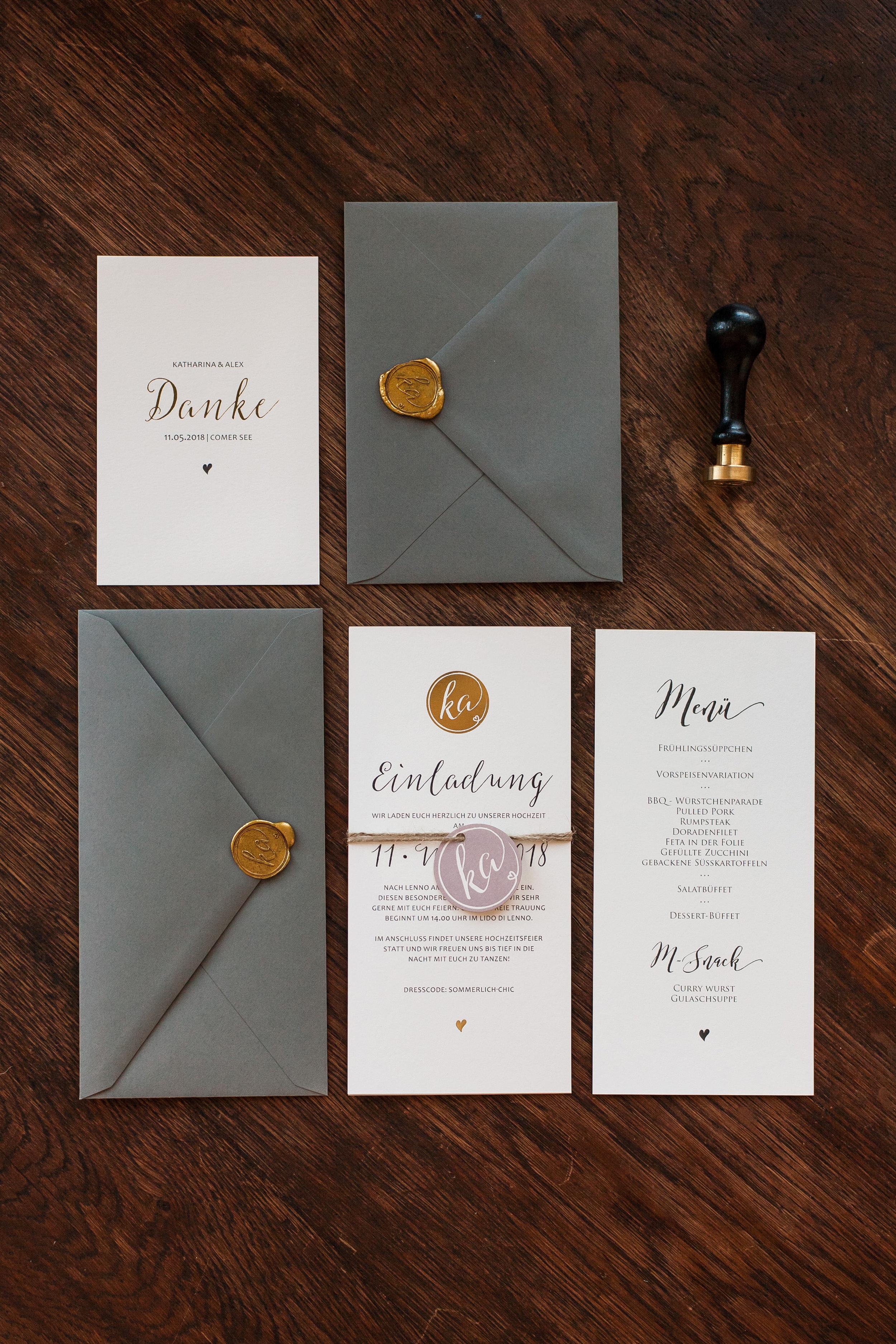 Hochzeitseinladung aus zwei Flachkarten mit Anhänger gebunden und grauem Briefumschlag und goldenem Siegel, Menükarte, Dankeskarte mit grauem Briefumschlag und goldenem Siegel