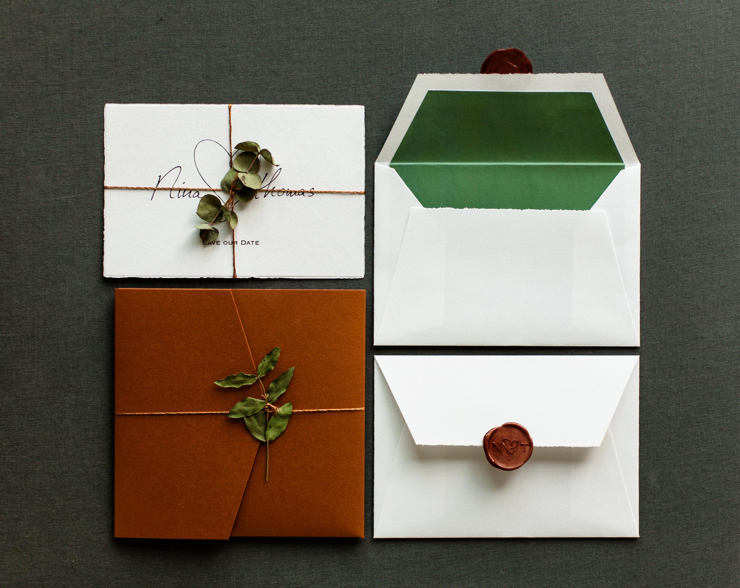 Pocketfold Einladung Kupfer und Save the Date Karte mit Kupferkordel und Eukalyptus, weißer Briefumschlag mit grünem Innenfutter und Kupfer Siegelstempel