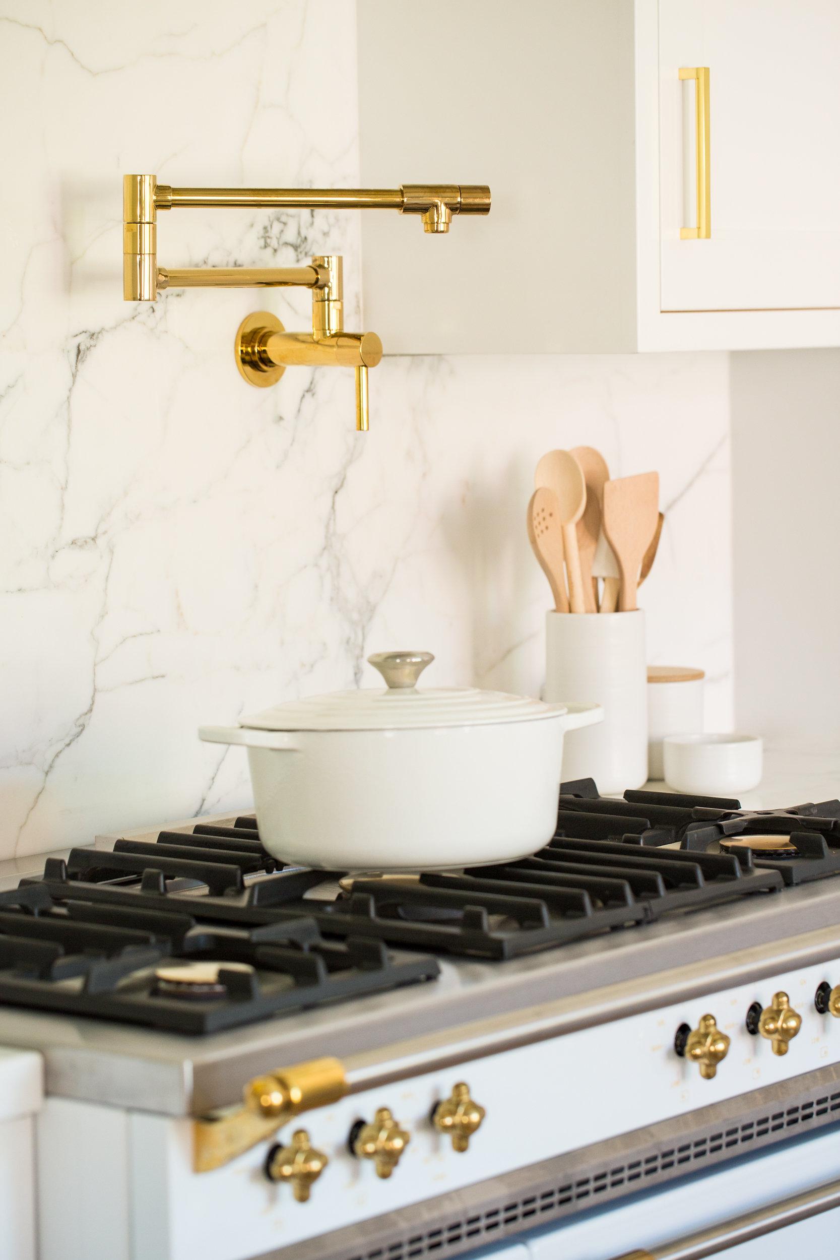 white lacanche stove gold hardware kitchen carrera marble counter backsplash danish scandinavian pantry hood
