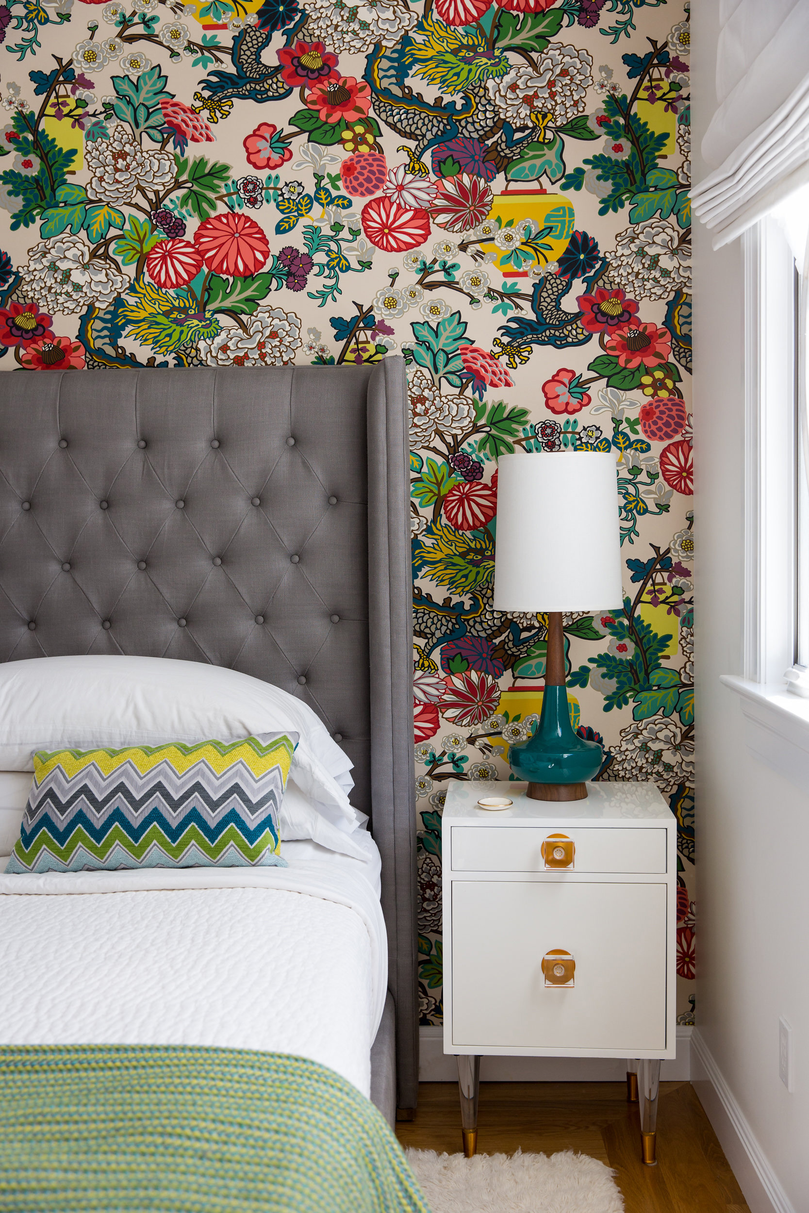 chiang mai dragon wallpaper bedroom headboard wall vibrant teal mid century lamp, white lacquer nightstand, schumacher