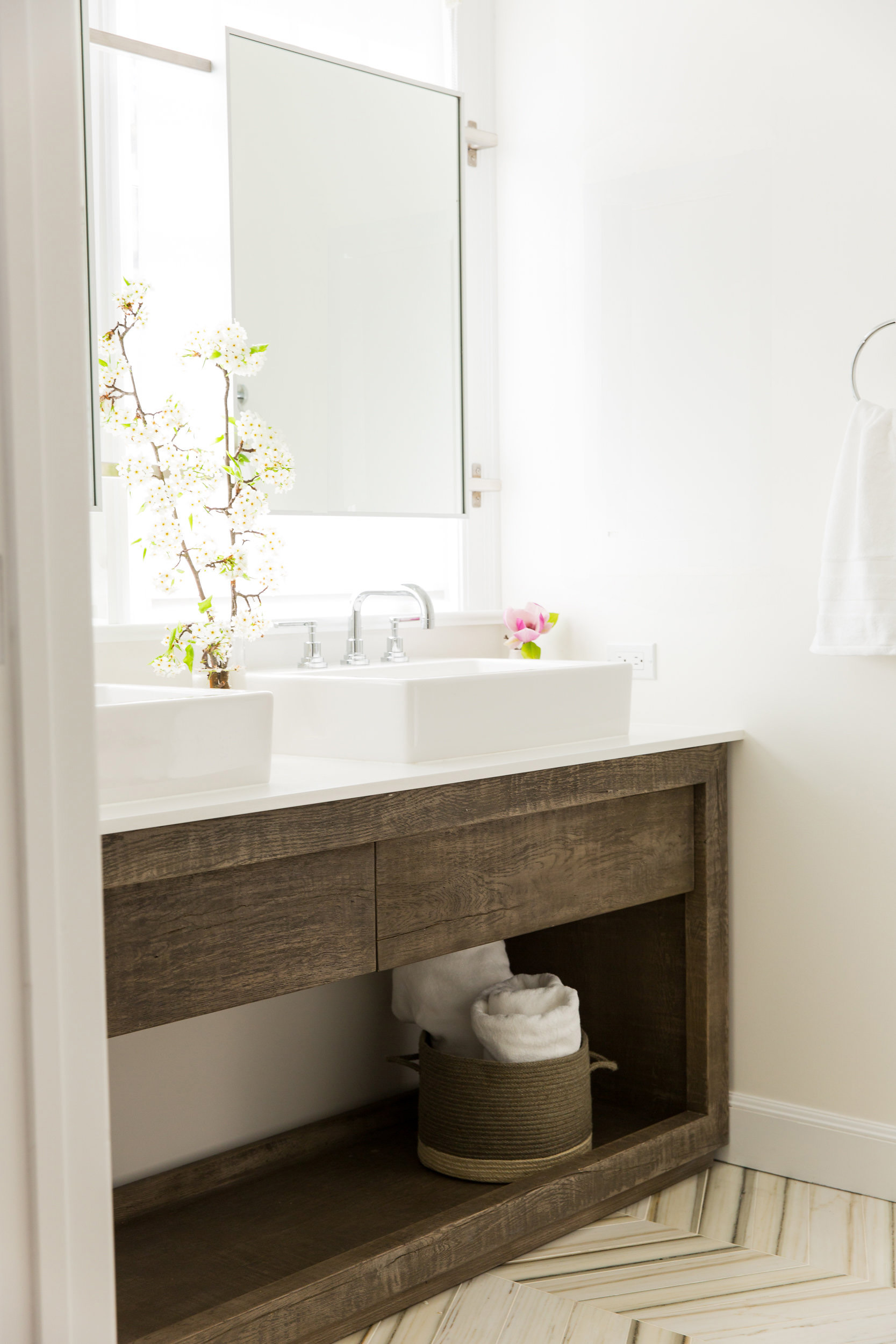 bathroom mirror in front of window chevron marble tile open storage above counter sink vessel