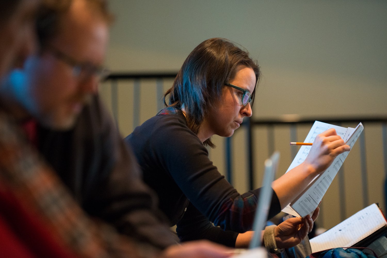 Carmen takes careful notes as she hears her composition come to life during first reading