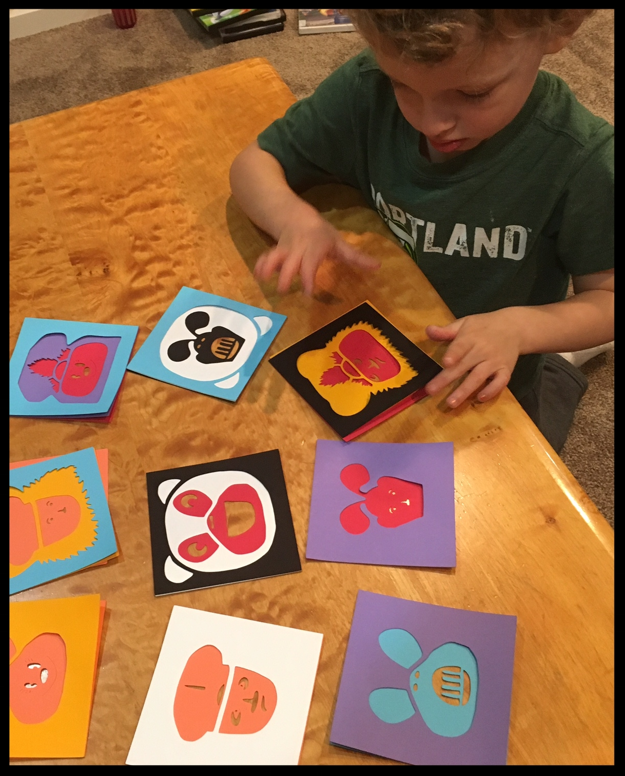 My three year old son interacts with layered paper cuts by mixing and matching designs and colored faces.