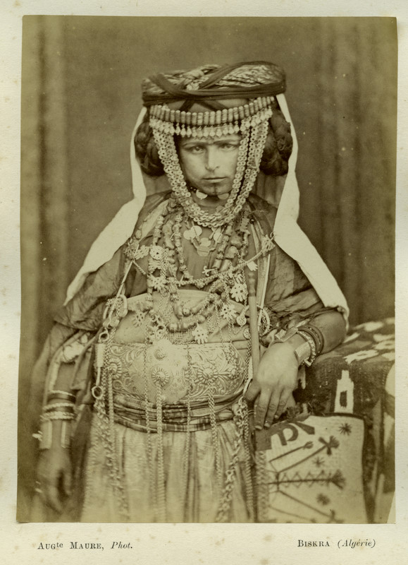 """by Auguste Maure <u><a href=""""https://commons.wikimedia.org/wiki/Category:Ouled_Nails#/media/File:Ouled_Nail_Biskra.jpg"""">via</a></u> Wikimedia Commons"""