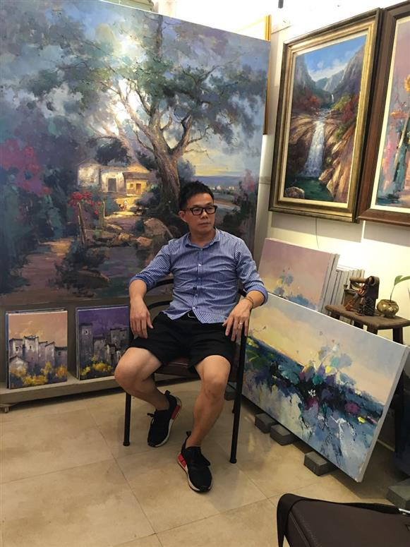 Chinese artist Jingshen You posing with his artwork