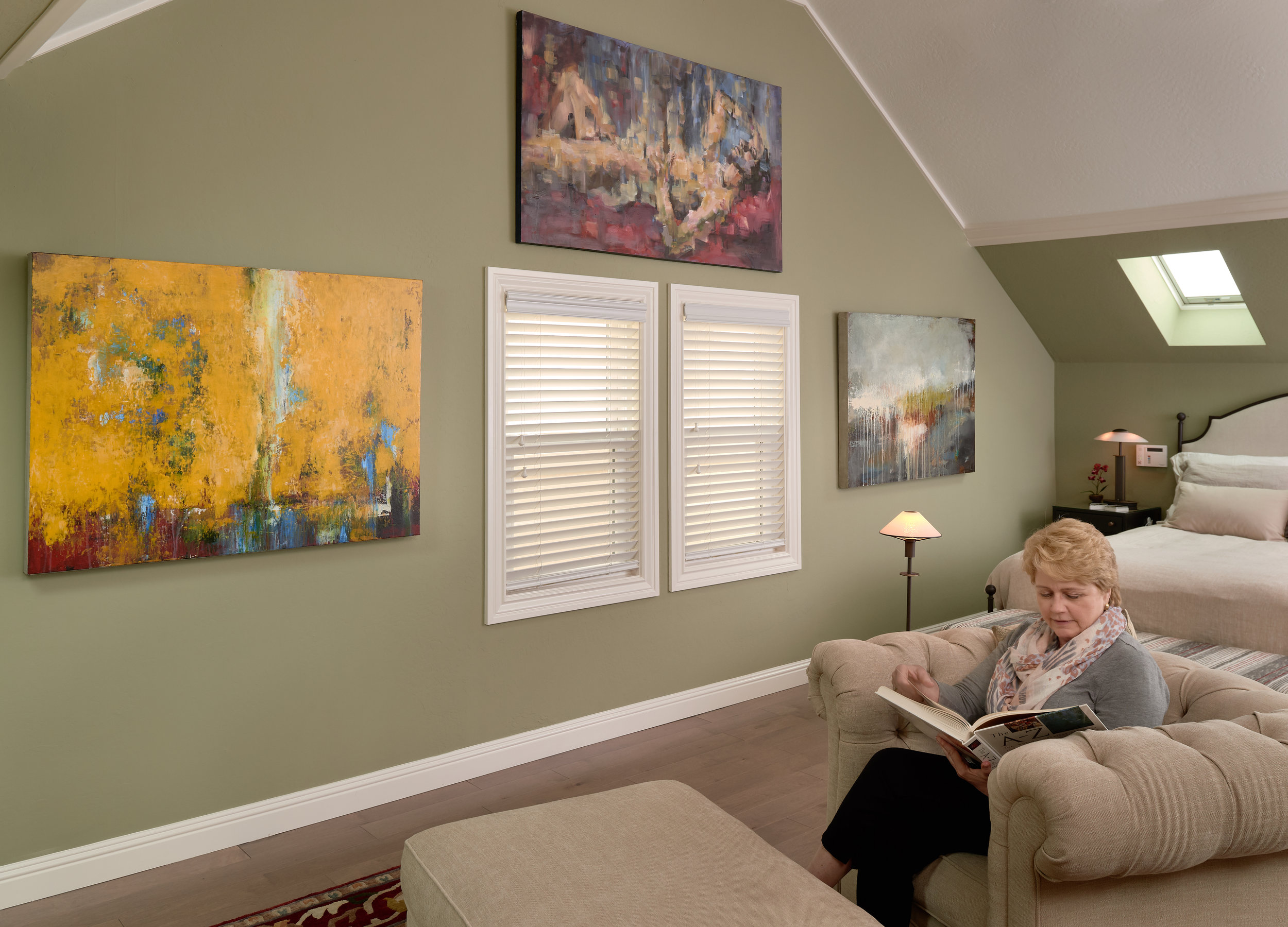 C.H. sitting by her UGallery paintings  Horizon  by  Faith Taylor  (left), Repose  by  Michele Giulvezan-Tanner  (center),  Breakthrough  by  Faith Taylor  (right)