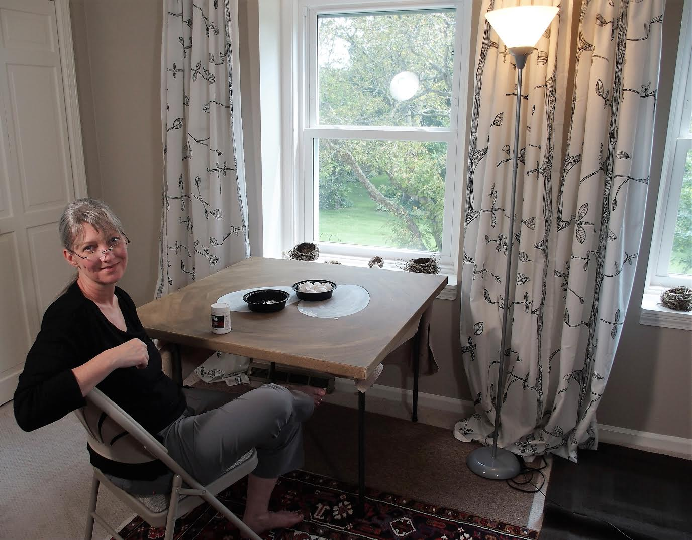 UGallery Artist of the Week Jennifer Ross sitting at her workspace working on   Each Must Enter the Nest