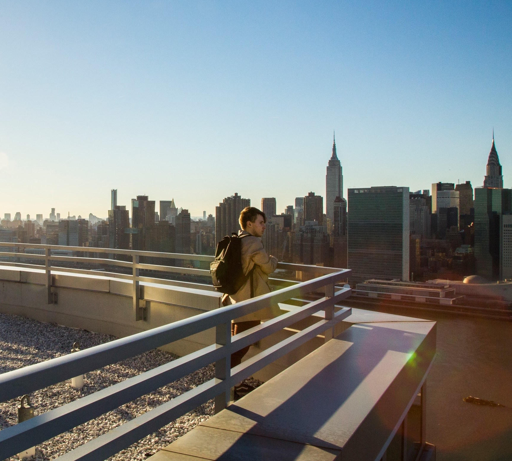Anthony Sokolov  on top of his building looking onto the Manhattan skyline