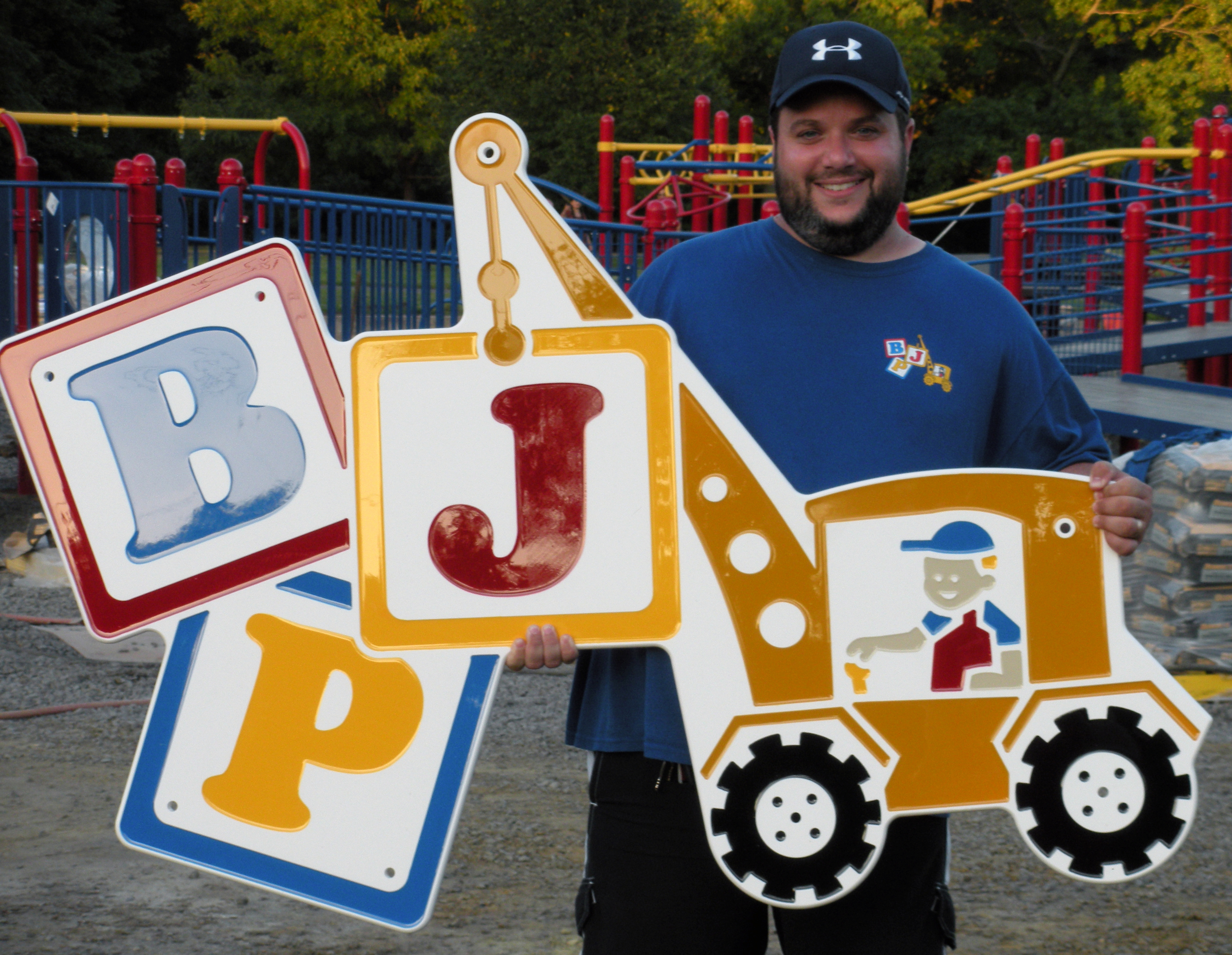 During the 3-day playground community build, Joseph Nasto (Co-Founder/President) holds the BJP logo that goes atop the archway leading to Jake's Place.