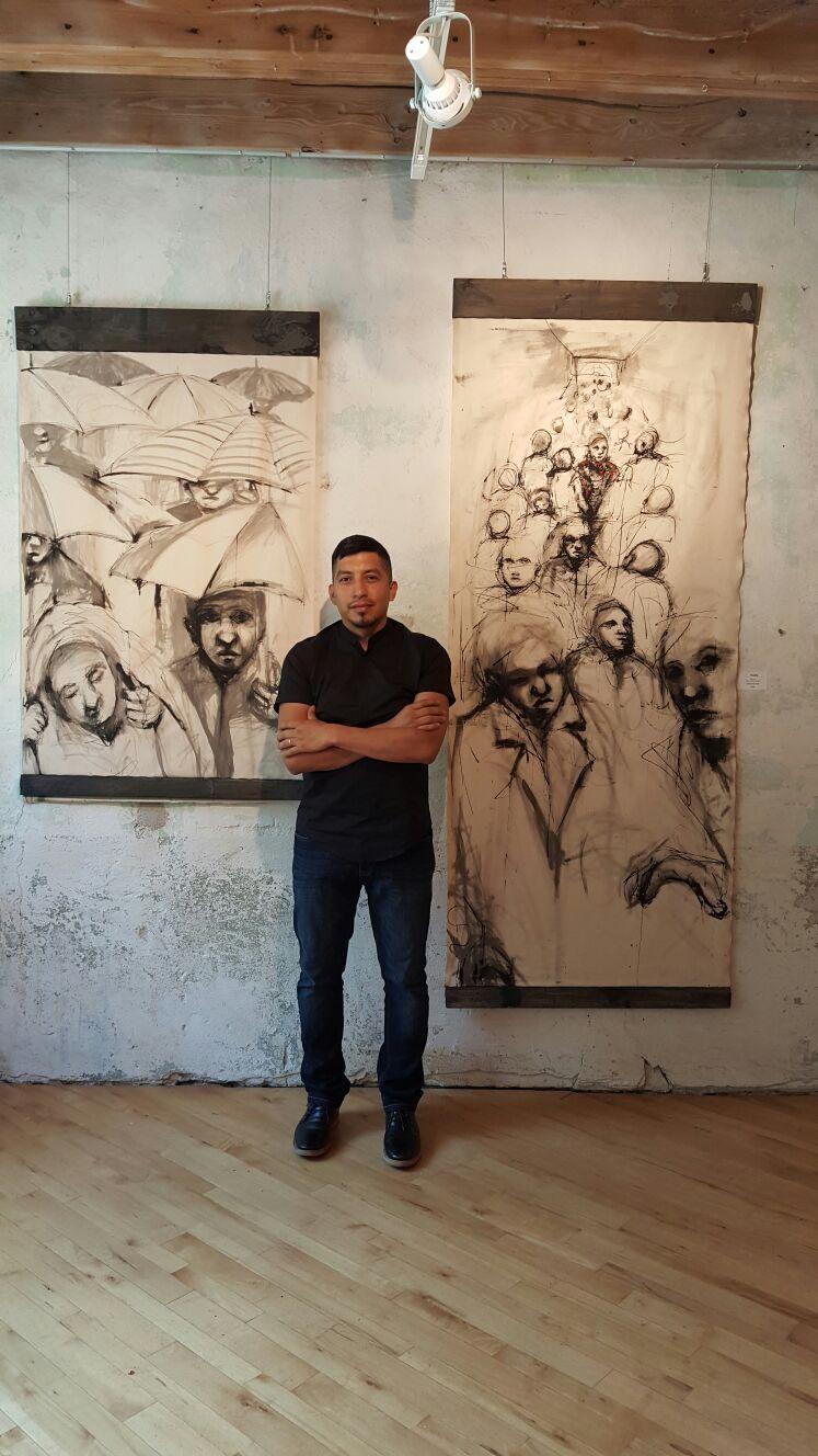 Carlos Delgado with two of his contemporary art pieces in Bartlett Art Gallery.