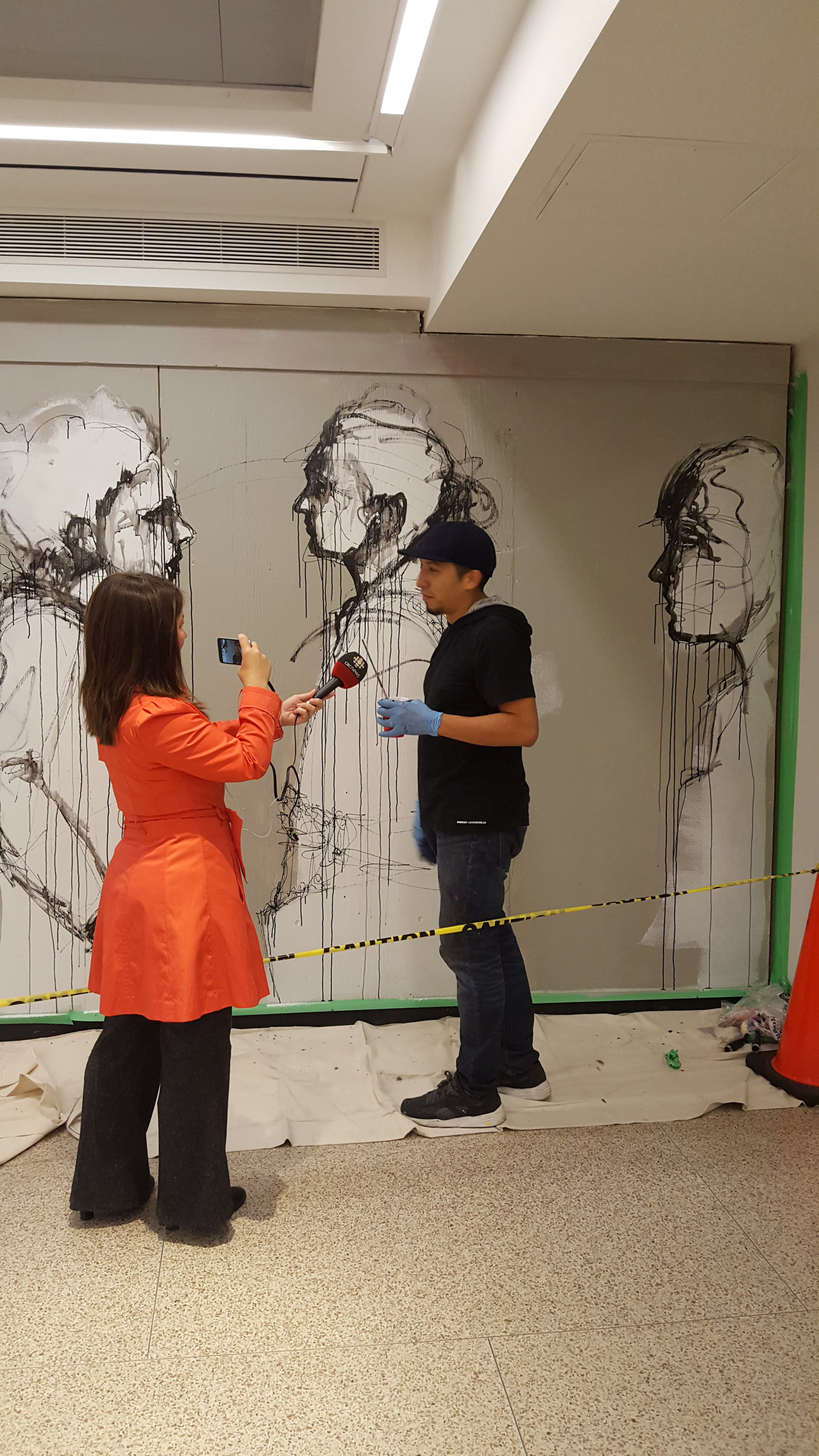 Carlos Delgado being interviewed by CBC News for live painting of mural in Union Station, Toronto