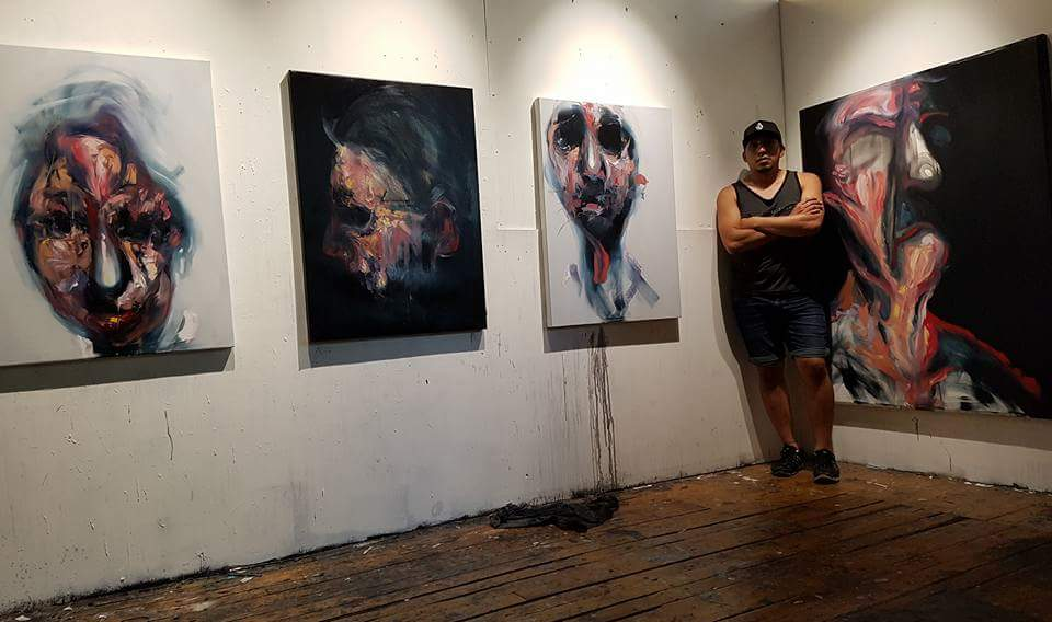 Artist Carlos Delgado in downtown Toronto studio with three new abstract portraits, original work