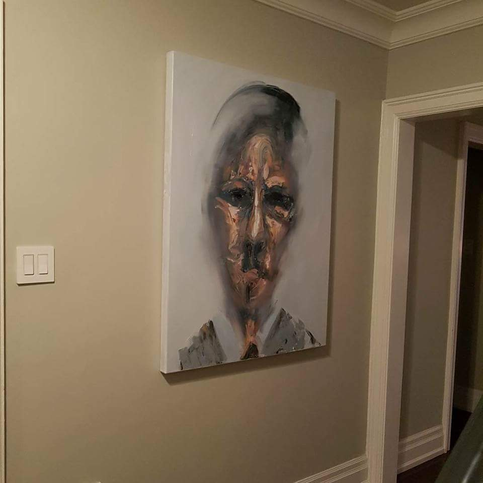 Abstract portrait with white background hung in lobby of hallway.