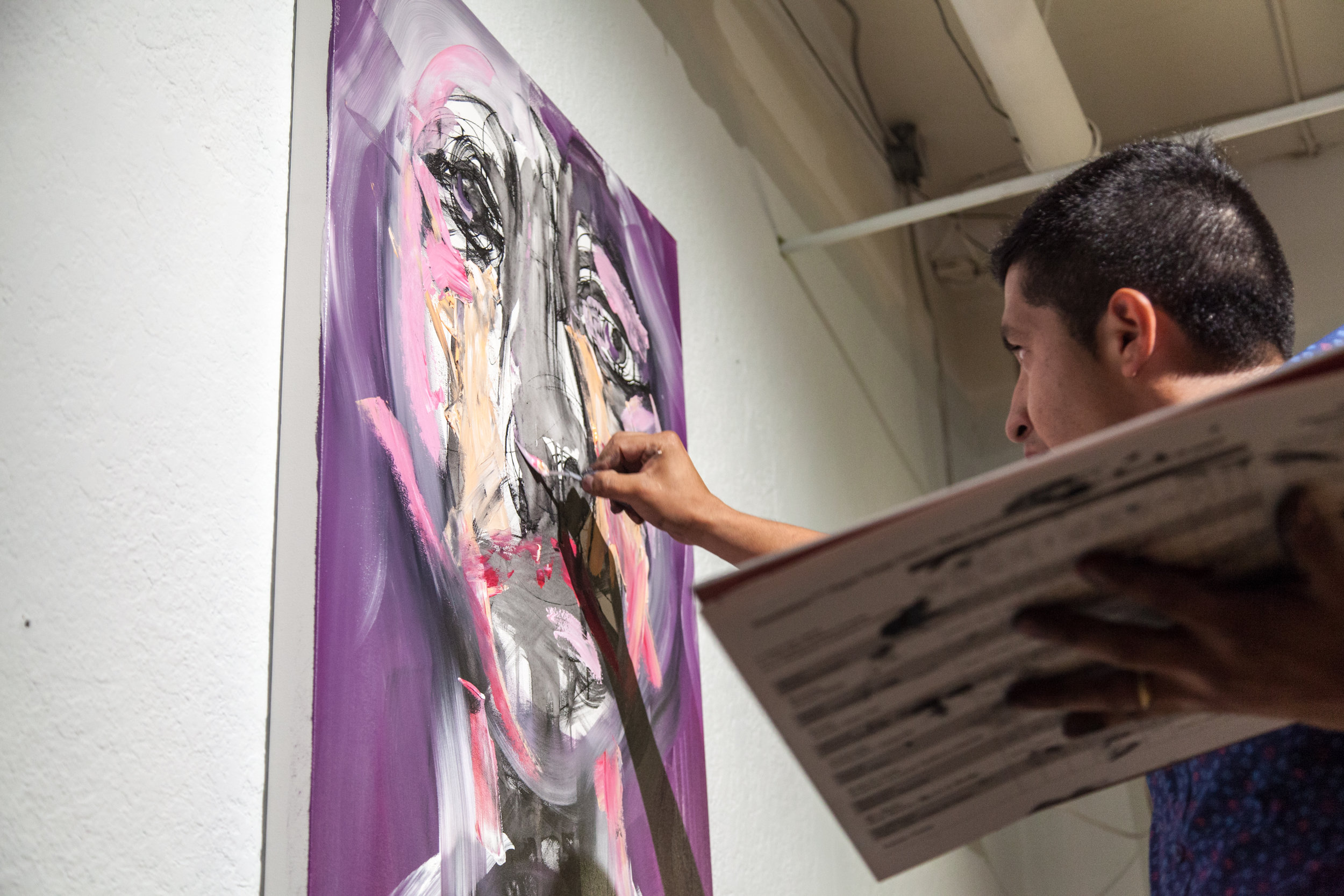 Live art painting at art show of abstract portraits by Colombian born, Toronto based artist Carlos Delgado in downtown Toronto at Orchid Signs.