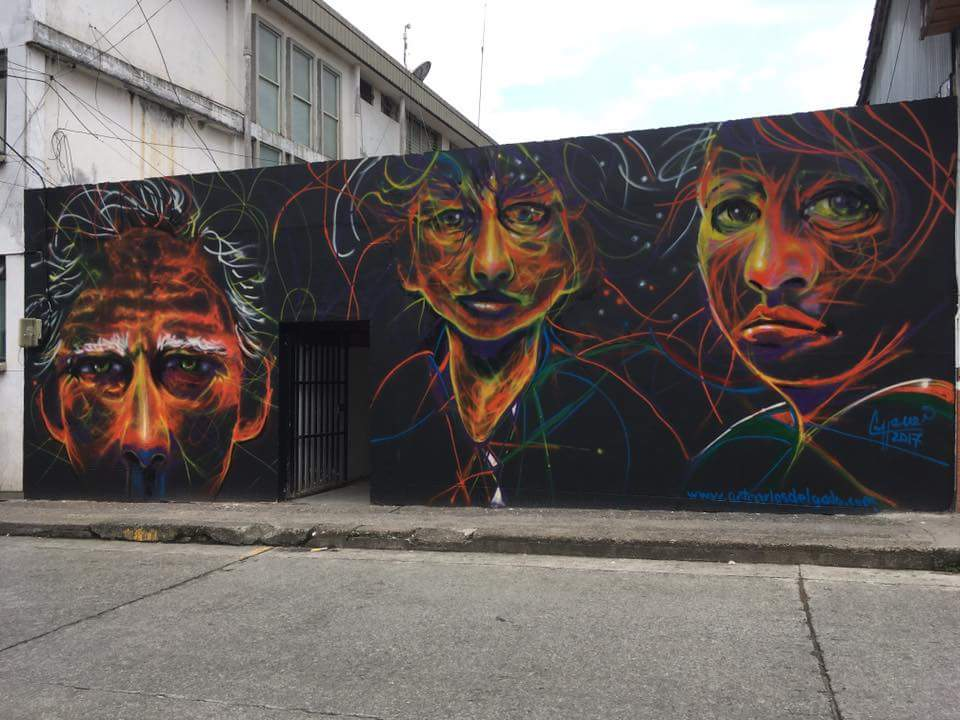 Black background and bold colours bring these abstract faces to life in this mural.