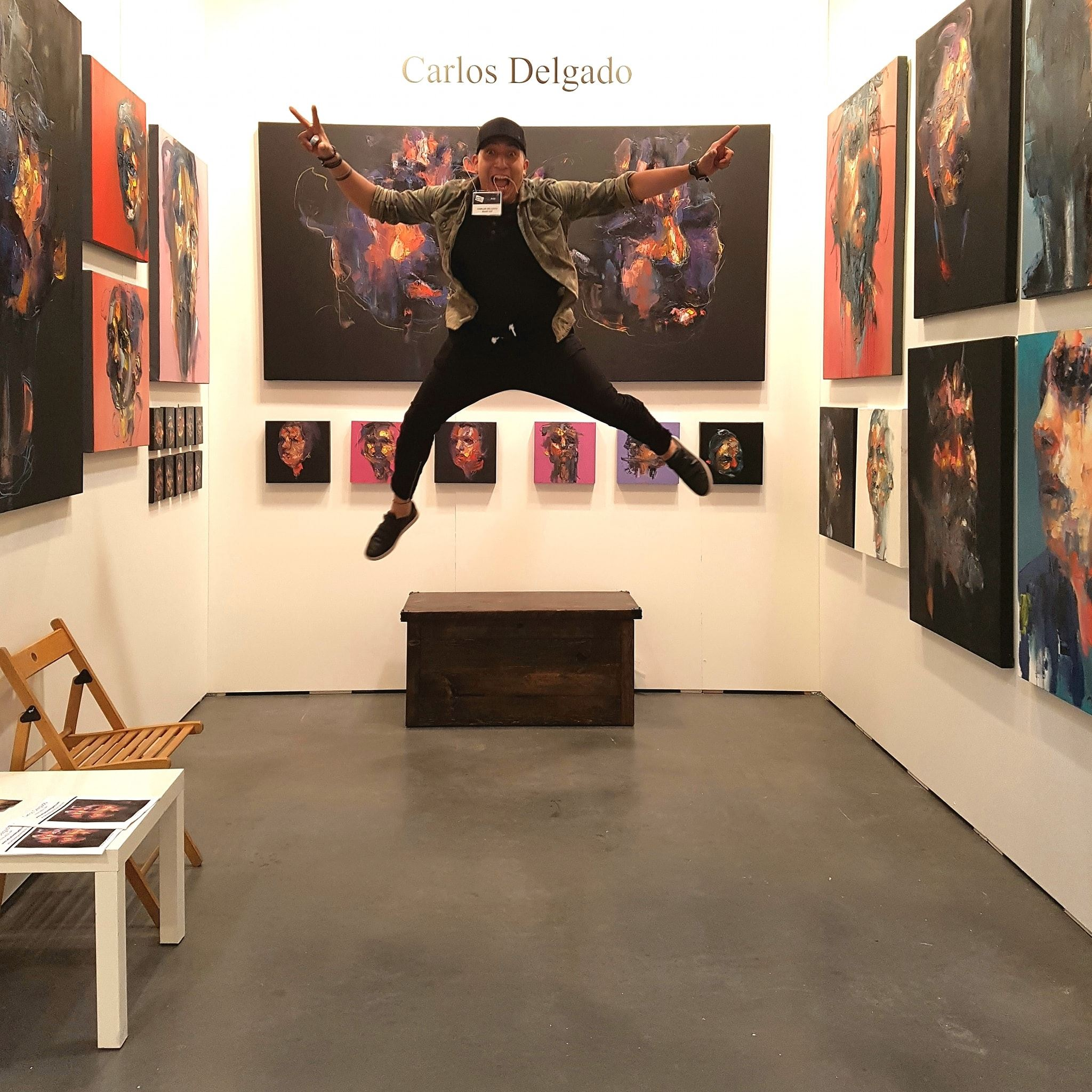 Visual artist Carlos Delgado jumping in front of his abstract portraits at Artist Project in Toronto 2018