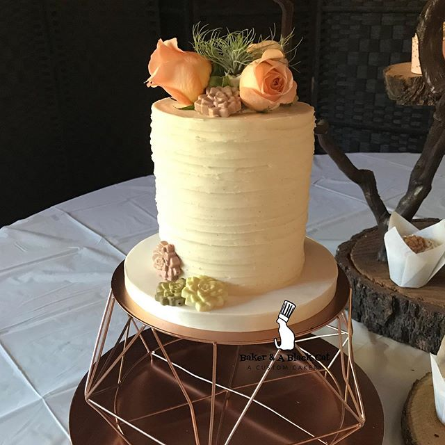 "A cute sweetheart cake for a sweetheart of a couple!! 5"" cake with fresh florals, chocolate succulents, and spun buttercream! . 📸: @bakerandablackcat 💐: @placervilleflowersonmain 🏞: @campnauvoo  Favorite cake stand ever provided by Trista & Anthony, and be careful guys, because I'm over here making grabby hands at it!!! .  #bakerandablackcat #cakesofinstagram #buttercreamcake #scratchmade #placervillebaker #campnauvoo #placervilleflowersonmain #realweddingsmag #placervilleweddings #stylemag"