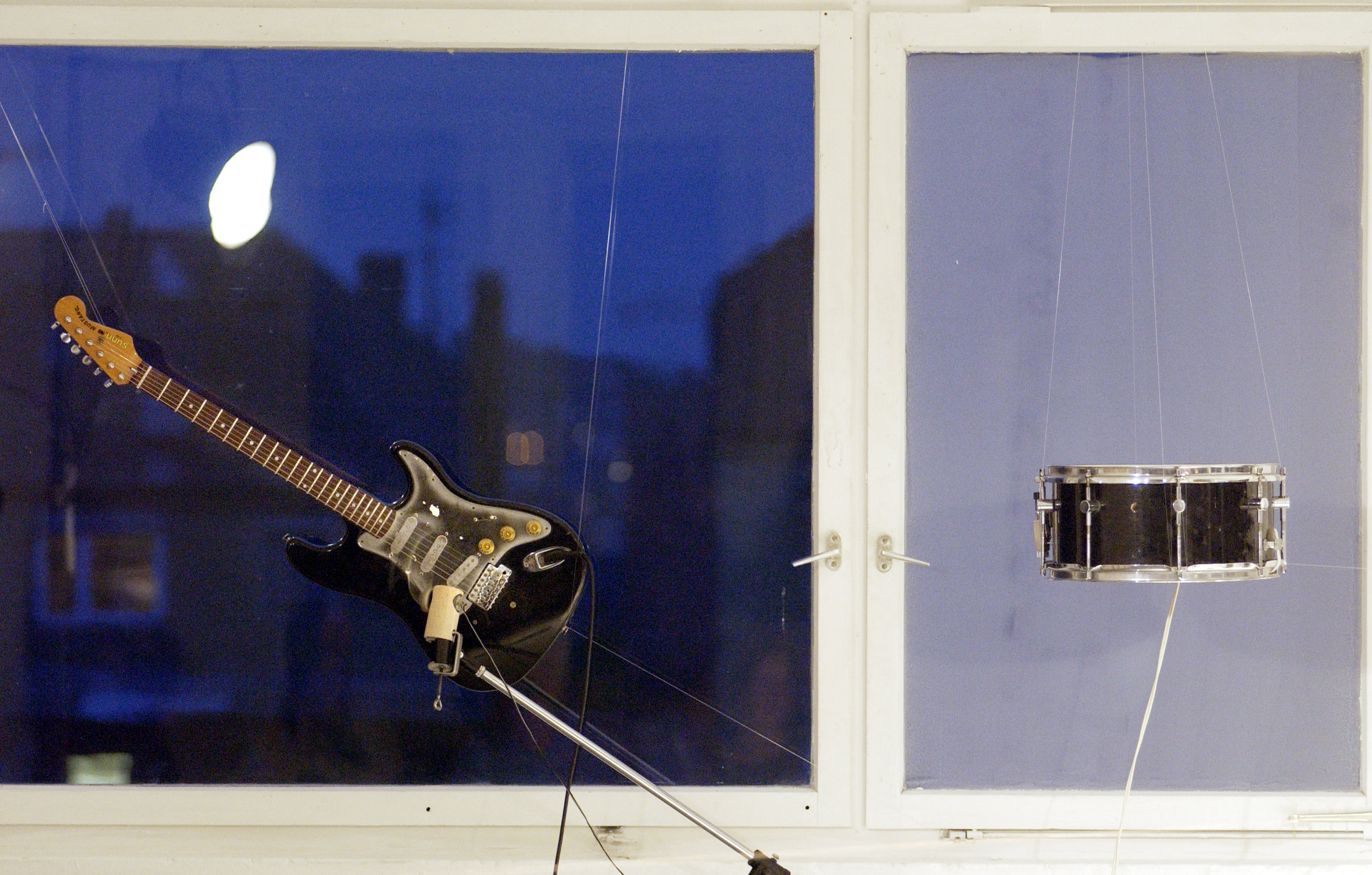 Konrad Sprenger installation, guitar strummed by motorized monofilament, snare drum resonated by an attached transducer playing sequencer files