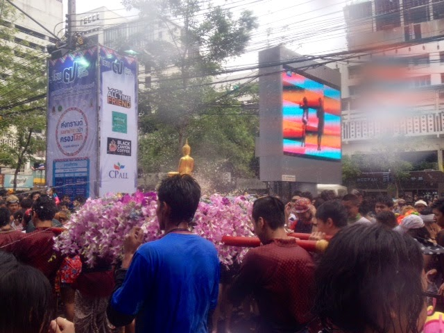 a procession with a Buddha statue passing through the Songkran party at Siam Square, Bangkok