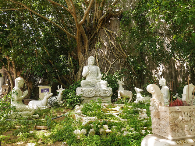 a marble statue of Buddha in the forest
