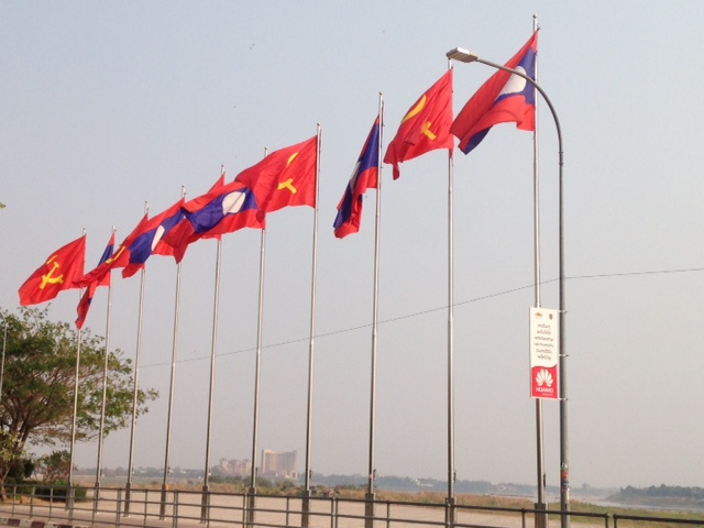 Lao flags flying above the Mekong Riverfront in Vientiane