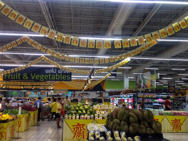 Je flags and signs at the produce section of a Thai supermarket