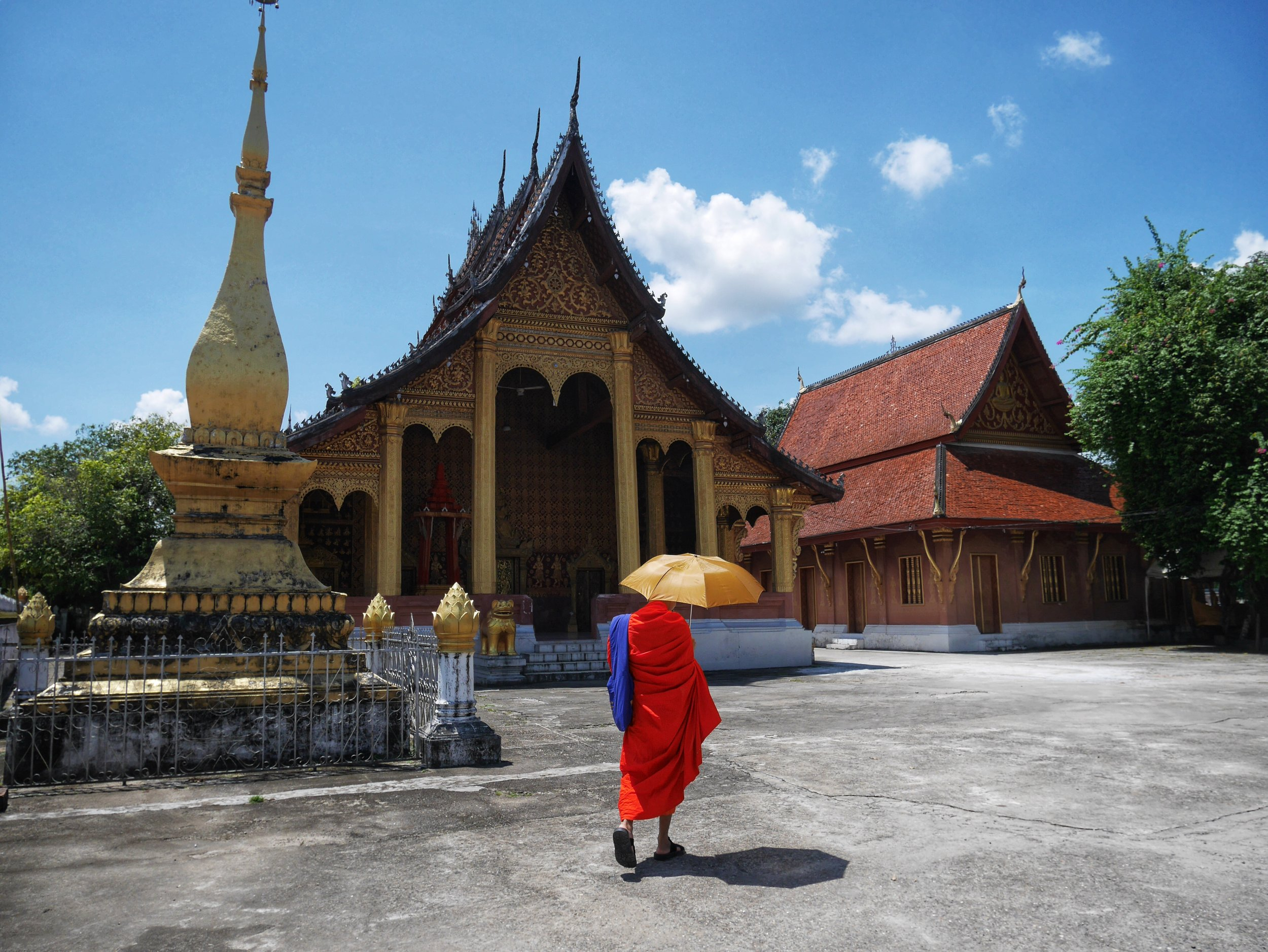 A Buddhist monk walking at a temple in Luang Prabang, Laos