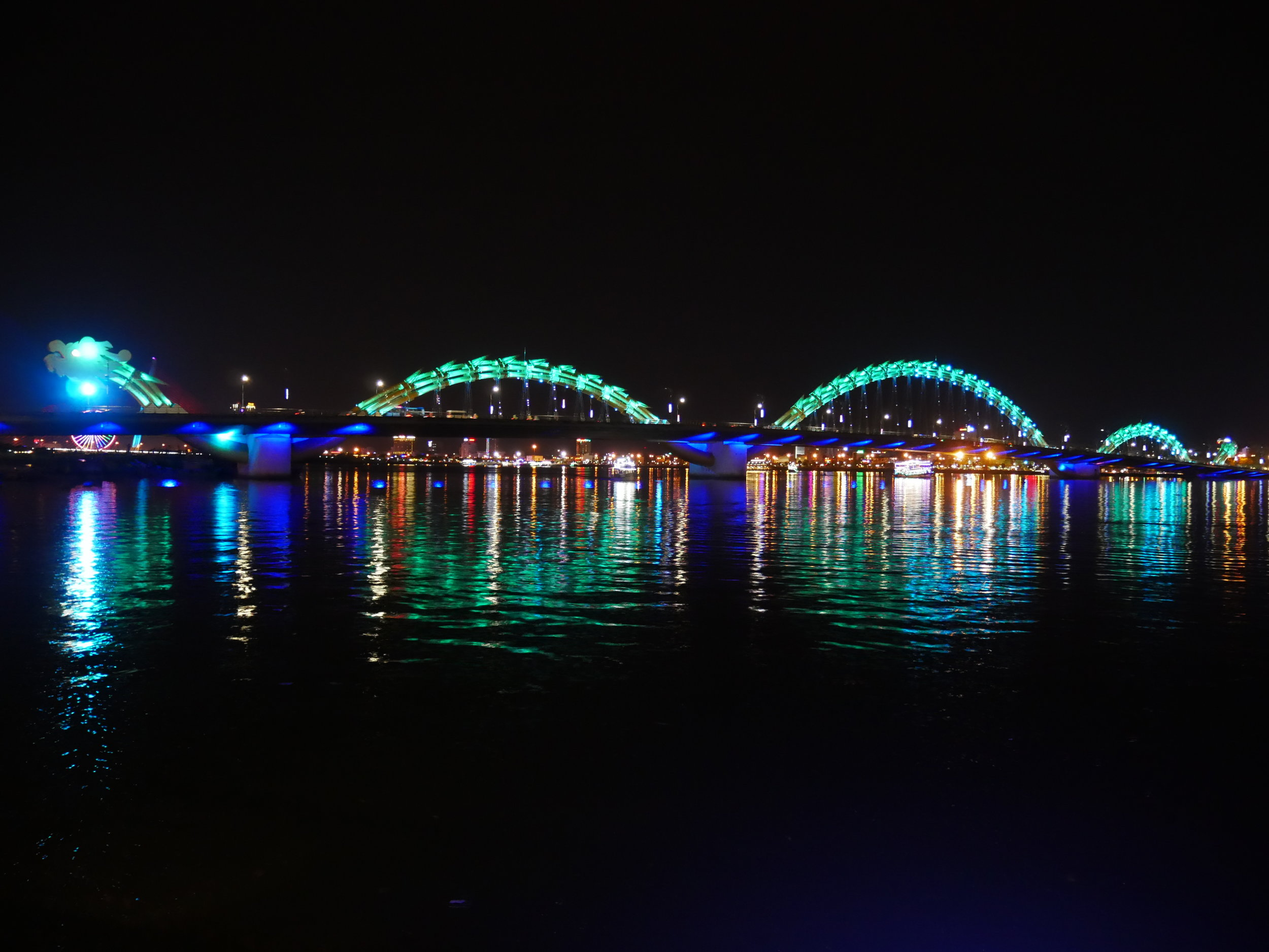 Dragon Bridge in Da Nang lit up with colorful lights at nighttime