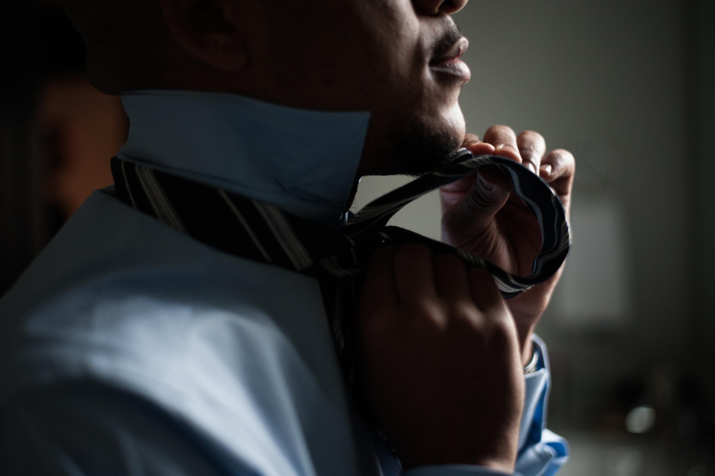 close up tying a custom tie on a blue custom shirt