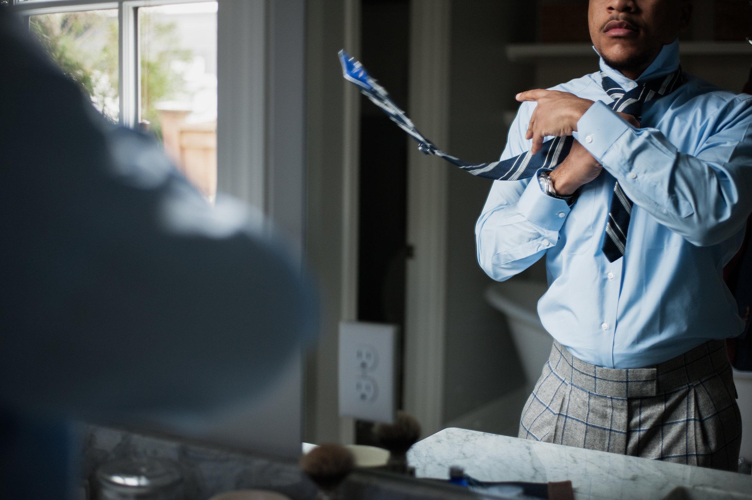 tying a custom blue tie on a custom blue shirt by stitch it shirt