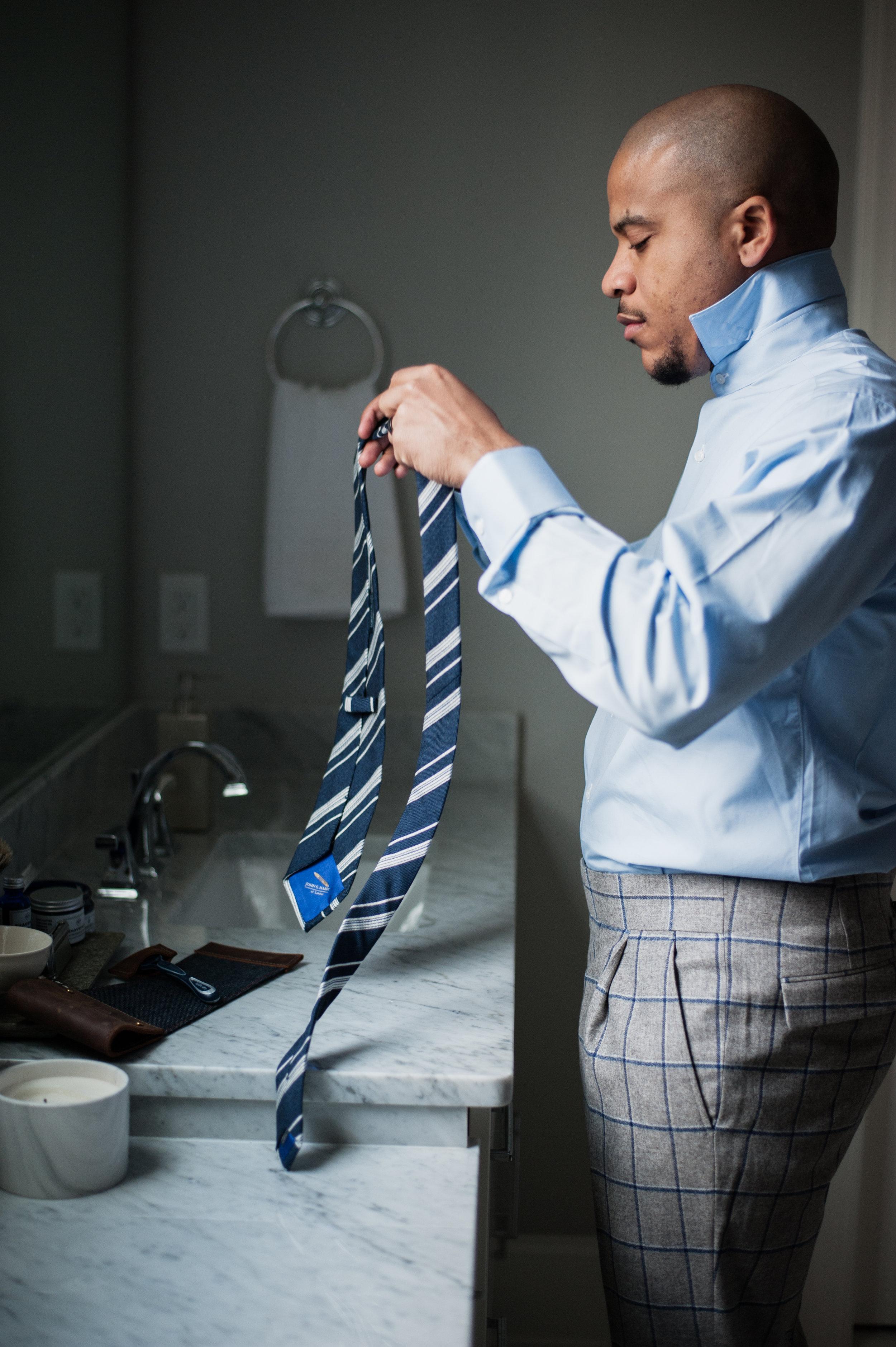 examining custom blue striped tie
