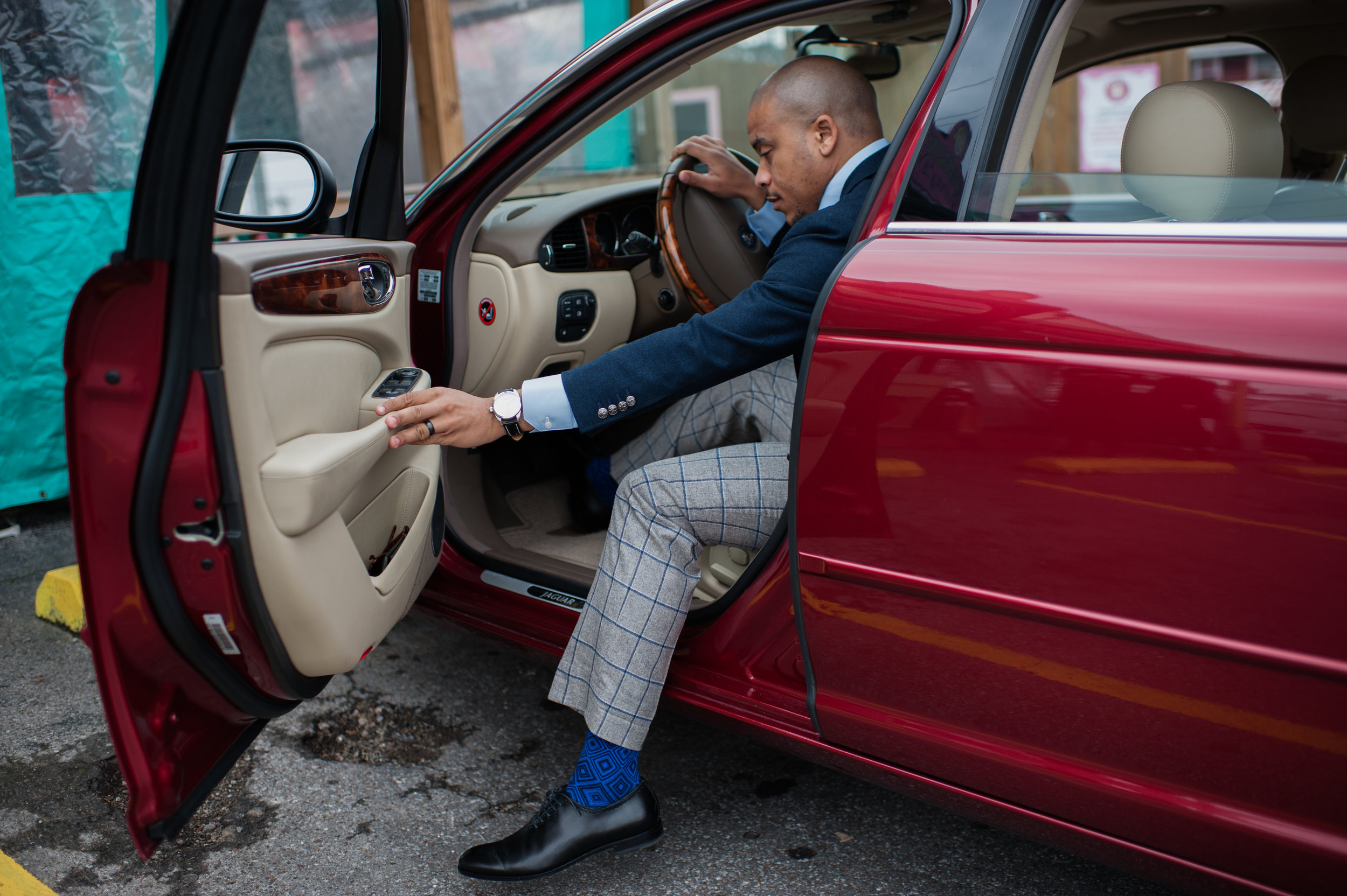 Man in custom suit getting out of red jaguar