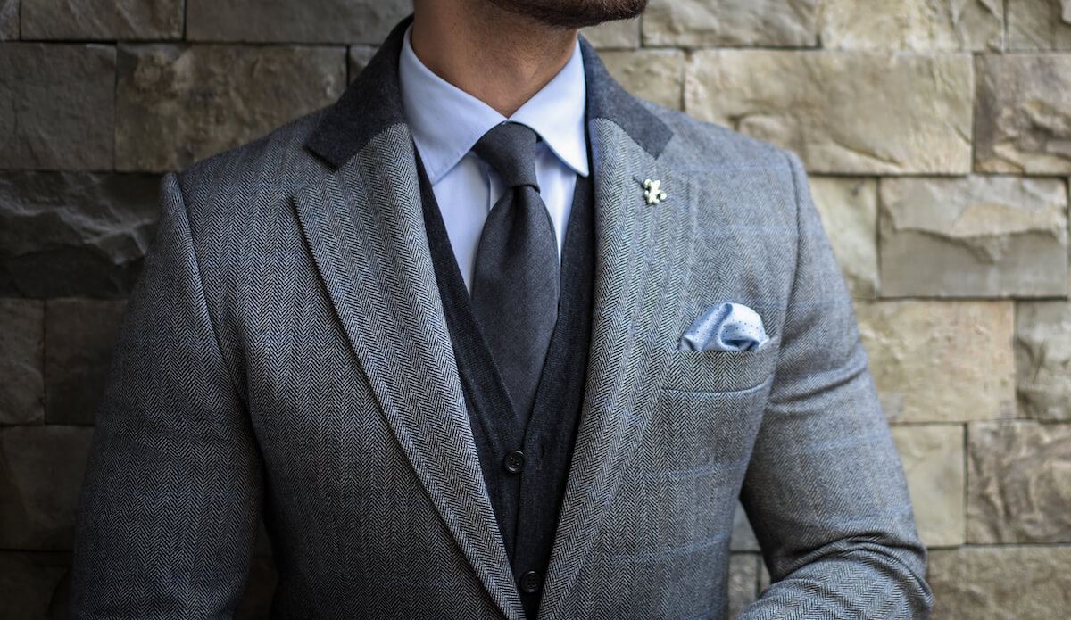 gray suit with light blue pocket square in a puff fold