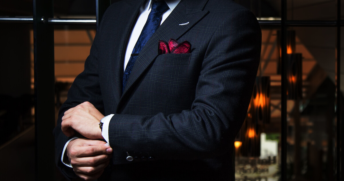 dark suit with a red pocket square in the Aficionado's fold