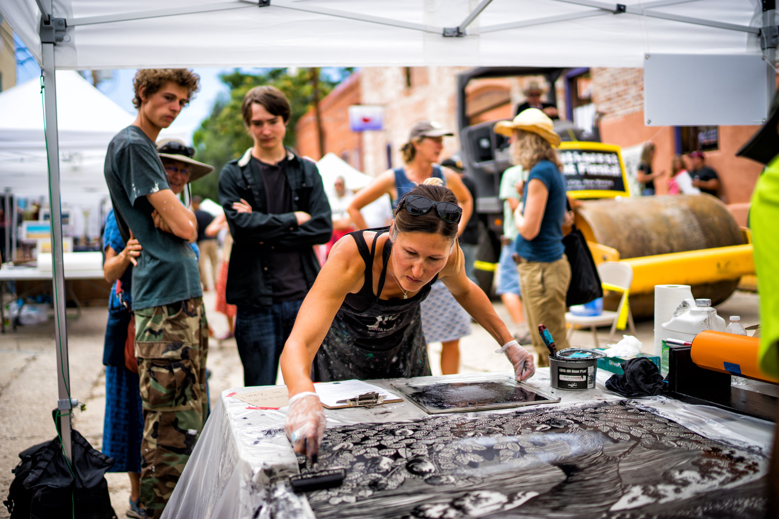 Inked by hand - Silver City local artist and educator, Stacey Heim, inks a large lineoleum block as visitors watch!