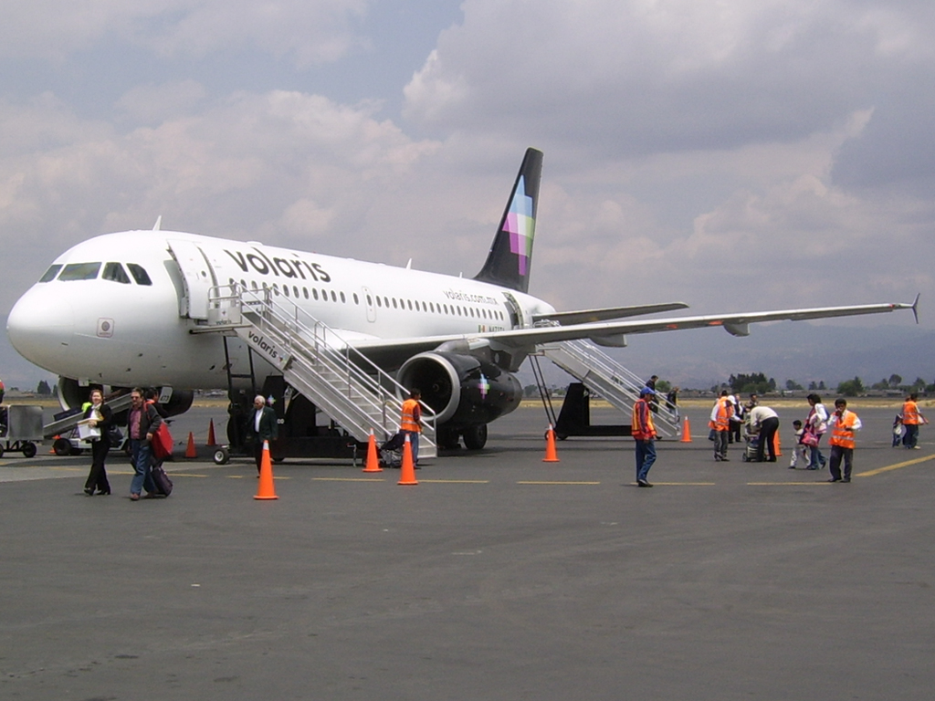 Volaris Airbus on the Tarmac... which also happens to be where they park because they don't pay for jetways in Cancun.