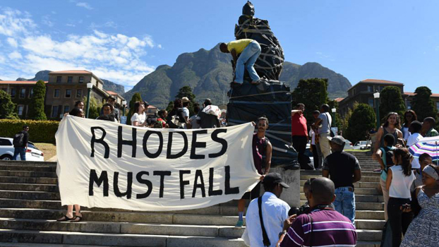 Photo from the internet depicting students protesting in front of a covered statue of Rhodes