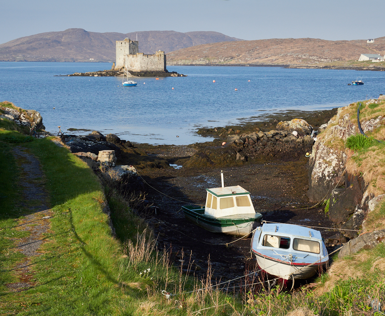 Kisimul Castle from the outskirts of Castlebay, with Vatersay in the distance