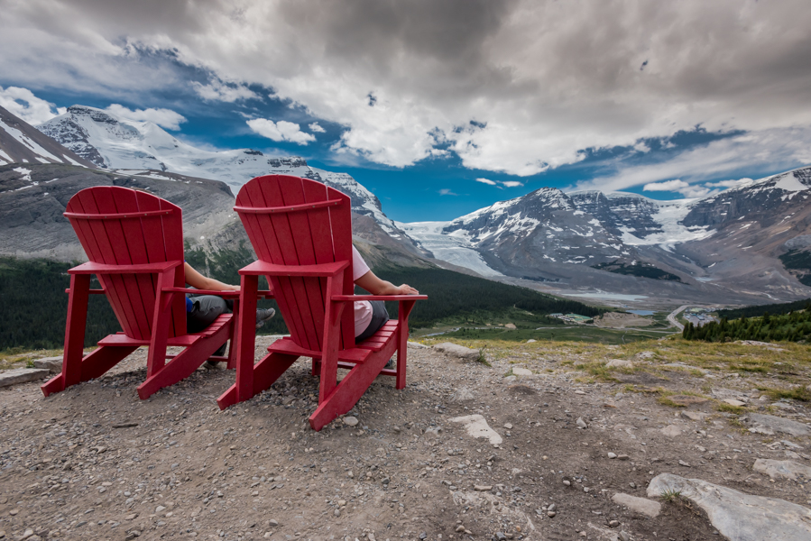 Behind View of Two People Sitting in Red Chairs